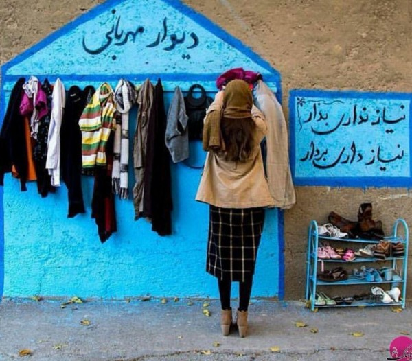 A girl in Iran, hangs a sweater on the Wall of Kindness to help protect the poor ones from harsh winter.