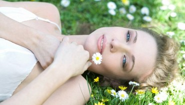 Young Woman Lying on Grass, Holding Flower, Smiling at Camera