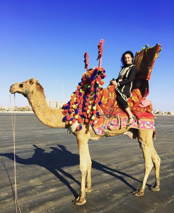 Sanam Chaudhry sitting on a camel